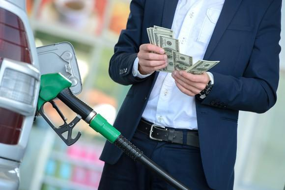 A man in a suit counting money while filling up a gas tank.
