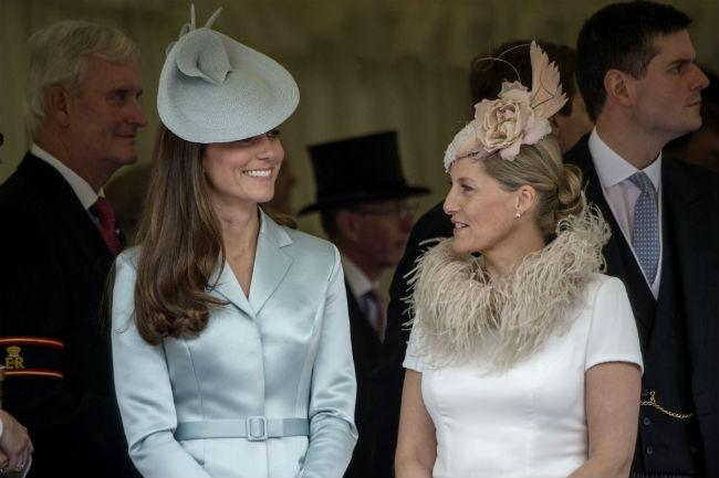 Kate Middleton standing next to Countess Sophie Wessex, both wearing elegant hats