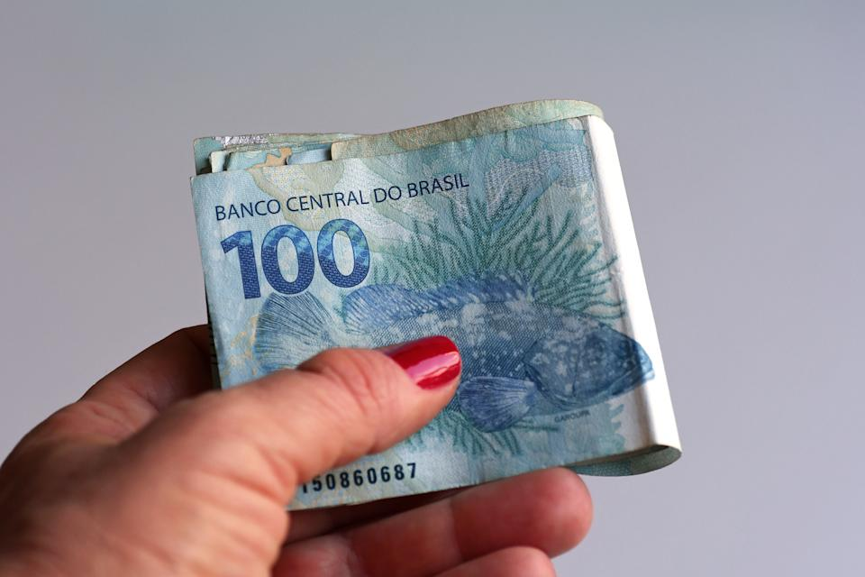 Female hand holding brazilian money (Real/Reais)