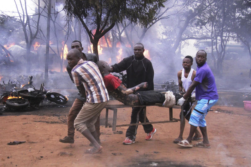 CORRECTING TO PETROL TANKER - An injured man is carried from the scene as a petrol tanker burns in the background, Saturday, Aug. 10 2019, in Morogoro, Tanzania. A damaged tanker truck exploded in eastern Tanzania Saturday as people were trying to siphon fuel out of it, killing at least 62, in one of the worst incidents of its kind in the East African country. (AP Photo)