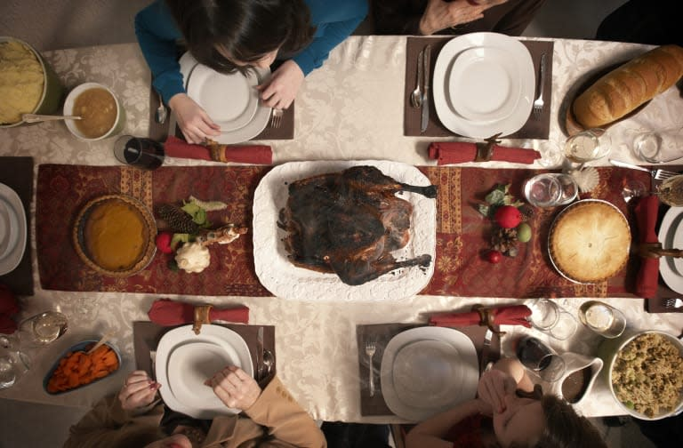 Family observing burnt turkey on dining room table