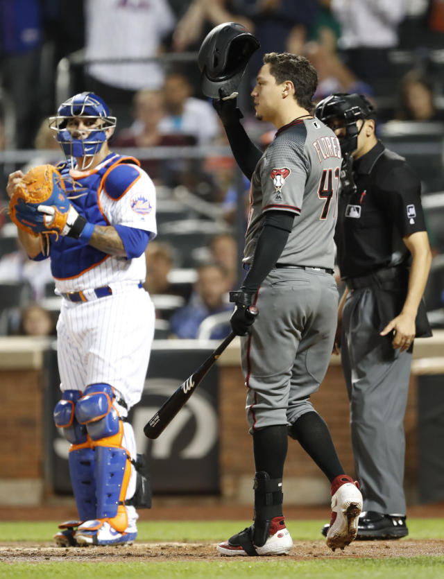 New York Mets' catcher Wilson Ramos, left, watches as Arizona Diamondbacks' Wilmer Flores (41) tips his helmet to the crowd as Flores's name is announced during the second inning of a baseball game Monday, Sept. 9, 2019, in New York. Flores is a former Met. (AP Photo/Kathy Willens)