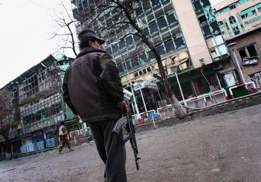 An Afghan security officer stands guard outside the Park Residence guesthouse (left) and Kabul City Center shopping center (right), the site of the gun battle and explosions, in Kabul in February 2010. A suicide attack at the entrance of the shopping mall and hotel in the Afghan capital Kabul killed two guards, an interior ministry spokesman said