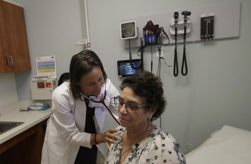 In this April 9, 2019 photo, Dr. Megan Mahoney, left, examines patient Consuelo Castaneda at the Stanford Family Medicine office in Stanford, Calif. Rapidly evolving technology and a surge in options like walk-in clinics or urgent care centers are creating many new front doors to health care instead of one main opening through the doctor's office. (AP Photo/Jeff Chiu)