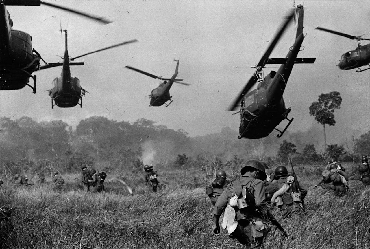 FILE - In this March 1965 file photo shot by Associated Press photographer Horst Faas, hovering U.S. Army helicopters pour machine gun fire into the tree line to cover the advance of South Vietnamese ground troops in an attack on a Viet Cong camp 18 miles north of Tay Ninh, Vietnam, northwest of Saigon near the Cambodian border. Faas, a prize-winning combat photographer who carved out new standards for covering war with a camera and became one of the world's legendary photojournalists in nearly half a century with The Associated Press, died Thursday May 10, 2012. He was 79. (AP Photo/Horst Faas, File)