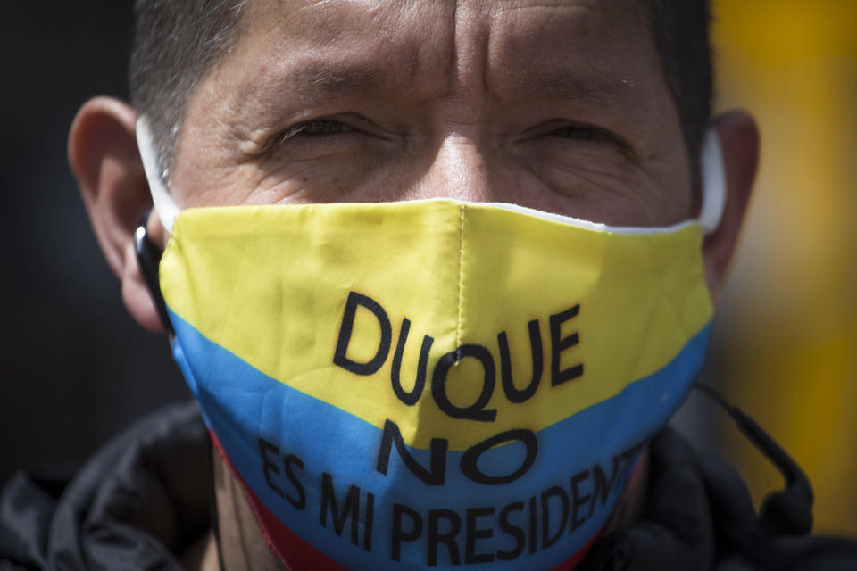 "A protester wears a mask with the Colombian flag colors and Spanish message ""Duque isn't my president,"" referring to President Iván Duque, during the march toward the residence of Bogota Mayor Claudia López to demand the lifting of the city-wide curfew and the reopening of business amid the COVID-19 pandemic in Bogota, Colombia, Wednesday, Jan. 20, 2021. (AP Photo/Ivan Valencia)"