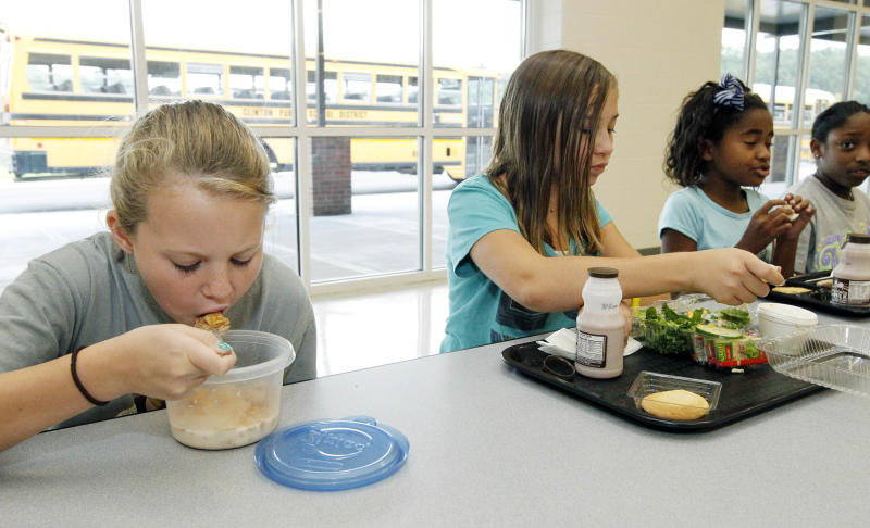 Rebekah Mizelle, 10, left, eats her cereal lunch as her friend and classmate Erin Bynum eats her school lunch Wednesday, Sept. 12, 2012 at Eastside Elementary School in Clinton, Miss. Students have several options for a nutritious lunch including bringing their own. (AP Photo/Rogelio V. Solis)