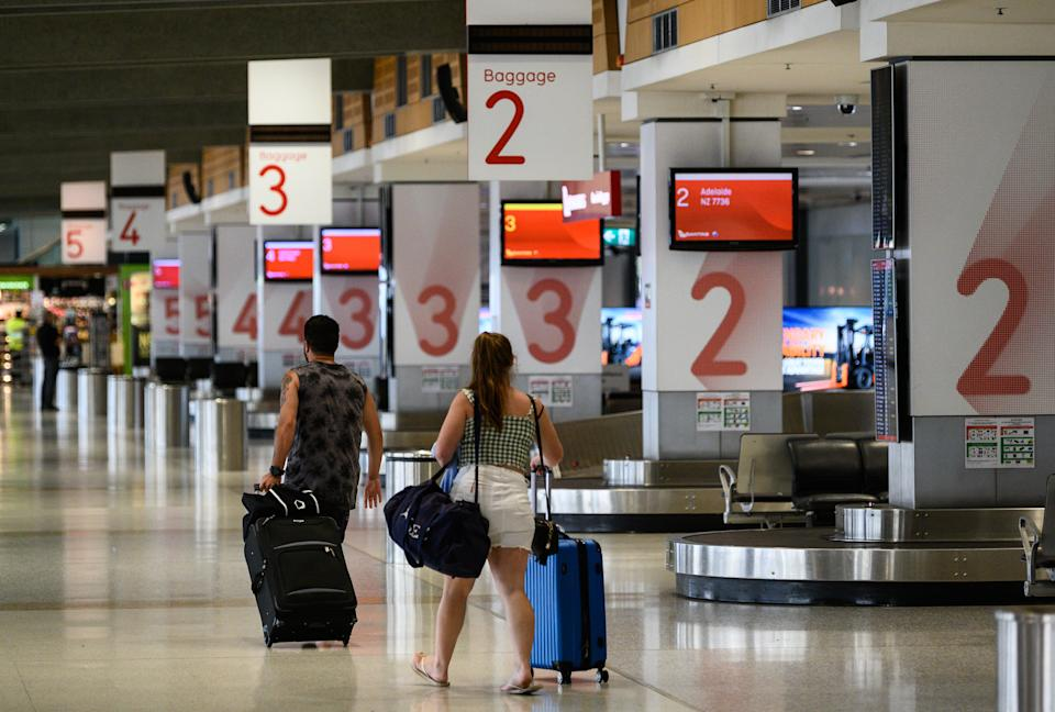 Passengers in an unusually quiet baggage arrivals area at Sydney Domestic Airport.