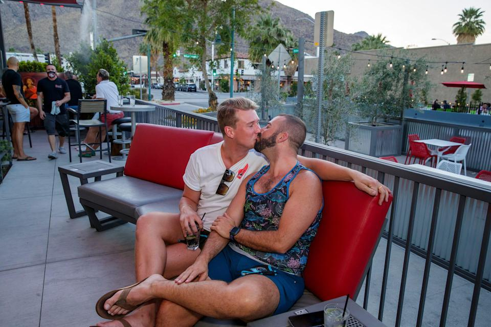 Josh Snyder, left, and Alex Ordoubegian of San Diego share a kiss at QuadZ Palm Springs on Arenas Road in Palm Springs, Calif., on Friday, April 30, 2021.