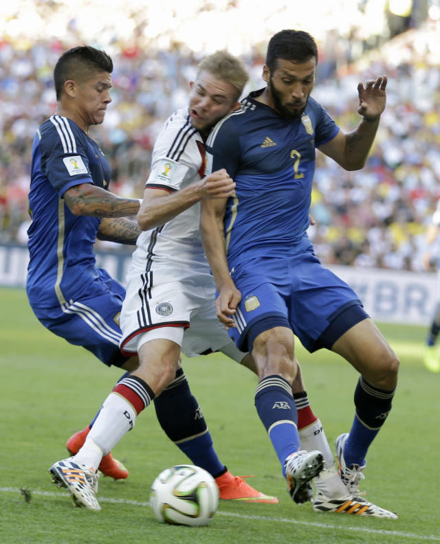 Germany's Christoph Kramer gets hit in the face by Argentina's Ezequiel Garay shoulder (2) while pinned between Garay and Marcos Rojo during the World Cup final soccer match between Germany and Argentina at the Maracana Stadium in Rio de Janeiro, Brazil, Sunday, July 13, 2014. (AP Photo/Natacha Pisarenko)