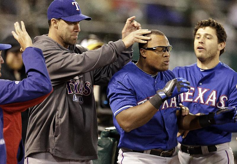 Texas Rangers' Adrian Beltre, center, is congratulated by teammates after hitting a home run off Oakland Athletics' Chris Resop in the tenth inning of a baseball game Tuesday, May 14, 2013, in Oakland, Calif. (AP Photo/Ben Margot)