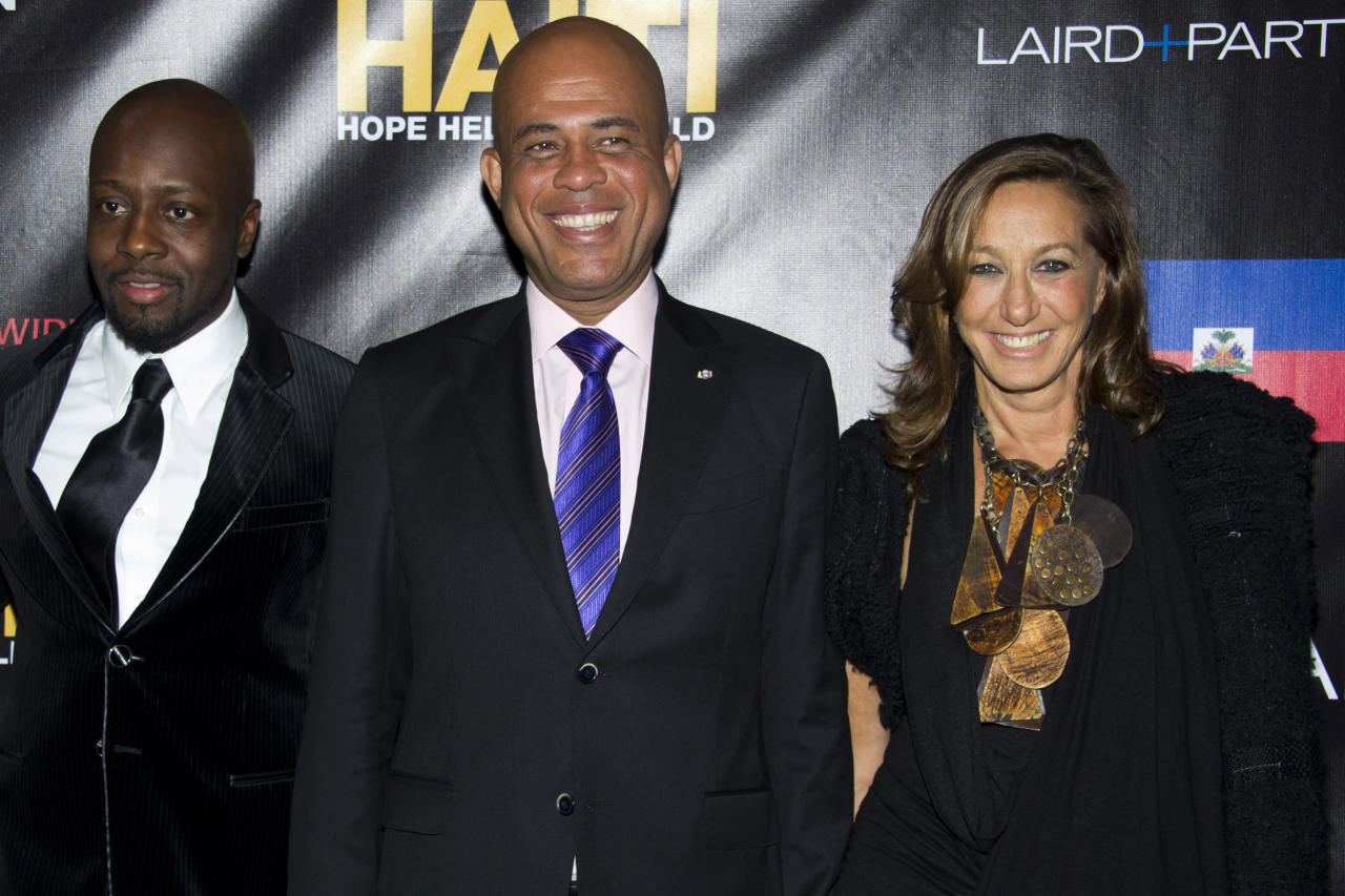 Wyclef Jean, Haitian President Michel Martelly and Donna Karan, left to right, attend a party to benefit Karan's Hope, Help and Rebuild Haiti charity, in New York, Tuesday, Sept, 20, 2011. (AP Photo/Charles Sykes)