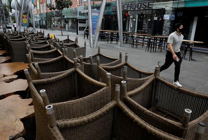 A man walks past chairs stacked up outside restaurants as dining-in is restricted to curb the coronavirus disease (COVID-19) outbreak in Singapore May 17, 2021.   REUTERS/Edgar Su