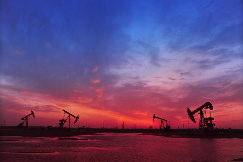 Oil pumps beneath a red and blue sky.
