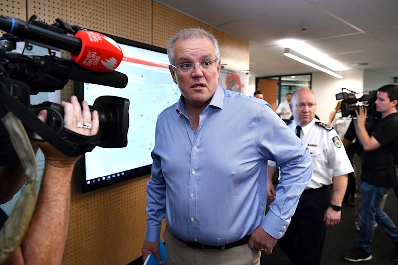 Prime Minister Scott Morrison is briefed by NSW RFS Commissioner Shane Fitzsimmons on Sunday morning. Source: AAP
