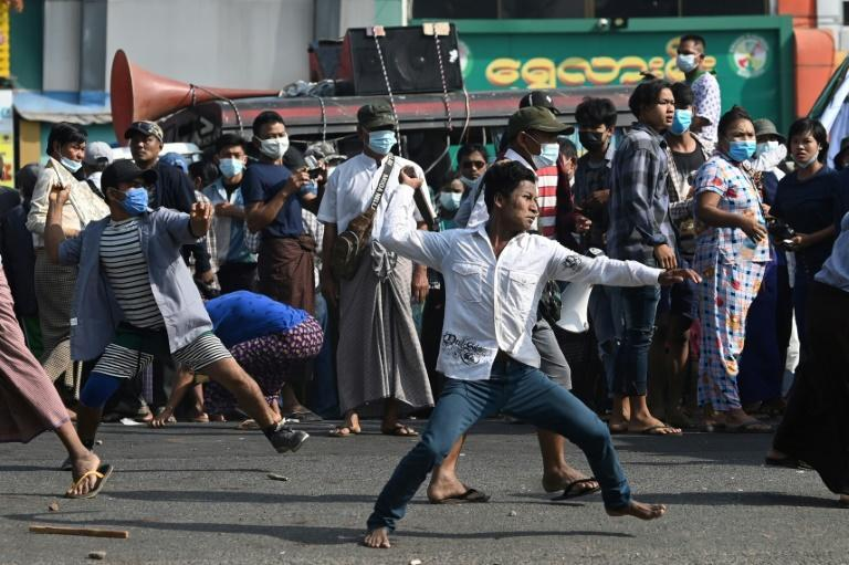 Supporters of Myanmar's military throw objects at residents in Yangon on Thursday
