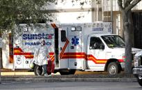 FILE PHOTO: A paramedic dressed in personal protective equipment exits an ambulance at St. Petersburg General Hospital in Florida