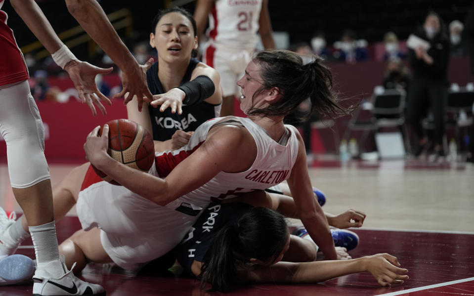 Canada's Bridget Carleton (6), center, falls on South Korea's Jihyun Park (9) in an attempt to grab the loose ball during women's basketball preliminary round game at the 2020 Summer Olympics, Thursday, July 29, 2021, in Saitama, Japan. (AP Photo/Eric Gay)