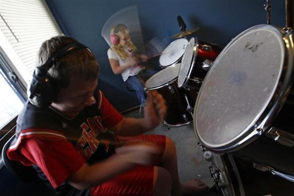 Parker Roos, who suffers from Fragile X, plays on a drum set with his sister Allison at his home in Canton, Illinois, April 4, 2012.