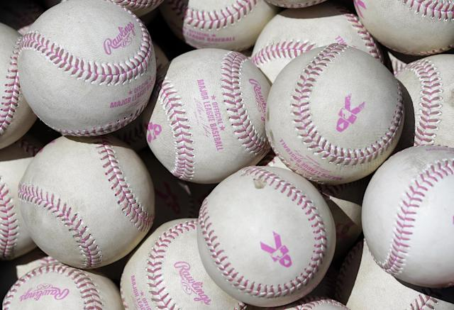Baseballs with pink stitching in honor of Mother's Day and breast cancer awareness sit in a bucket in the Baltimore Orioles dugout before a baseball game against the Houston Astros, Sunday, May 11, 2014, in Baltimore. (AP Photo/Patrick Semansky)