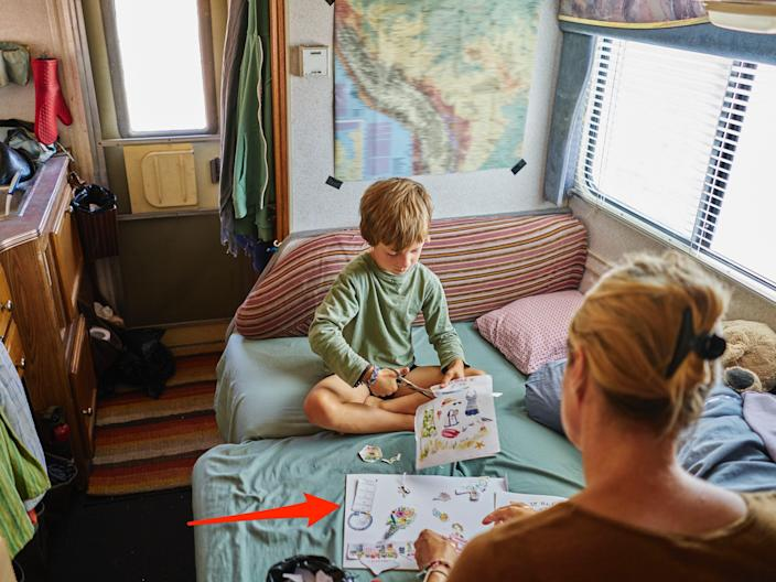 This image shows a mother and son cutting out pictures in camper van and an arrow pointing to a picture in the mom's hand