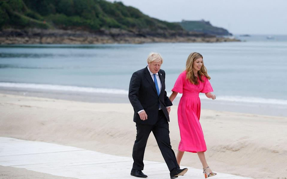 Boris Johnson and his wife Carrie Johnson heading for the 'family photo' - AFP