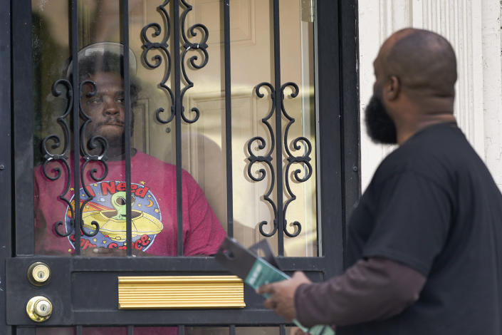 Anthony Brinson, right, talks with a resident while leaving a flyer at a home in Detroit, Tuesday, May 4, 2021. Officials are walking door-to-door to encourage residents of the majority Black city to get vaccinated against COVID-19 as the city's immunization rate lags well behind the rest of Michigan and the United States. (AP Photo/Paul Sancya)
