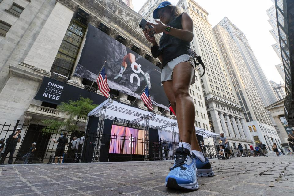A woman wears On shoes outside the New York Stock Exchange before the company's IPO, Wednesday, Sept. 15, 2021. (AP Photo/Richard Drew)