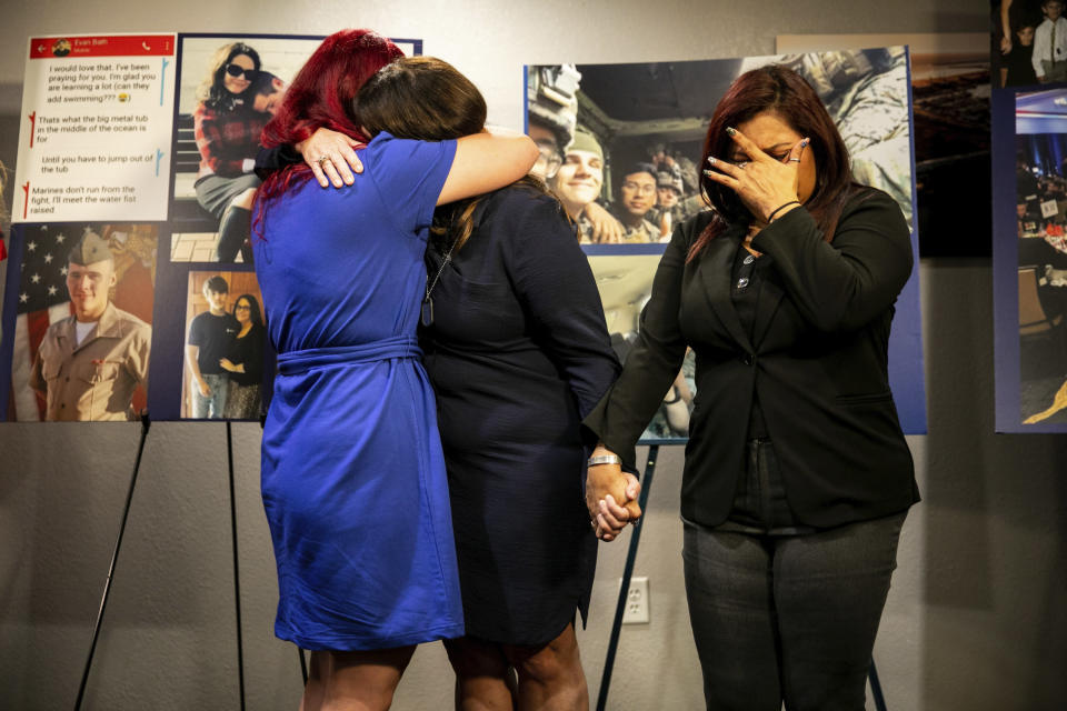 Christiana Sweetwood, left, mother of Marine Lance Cpl. Chase Sweetwood, Aleta Bath, mother of Pvt. 1st Class Evan Bath and Lupita Garcia, right, mother of Marine Lance Cpl. Marco Barranco embrace and hold each other at a press conference on Thursday, July 29, 2021, in Oceanside, Calif. The families of eight Marines and one sailor who died when their amphibious assault vehicle sank off the Southern California coast in the summer of 2020 plan to sue the manufacturer of the vehicle that resembles an armored seafaring tank, their lawyers announced Thursday. (Sam Hodgson/The San Diego Union-Tribune via AP)