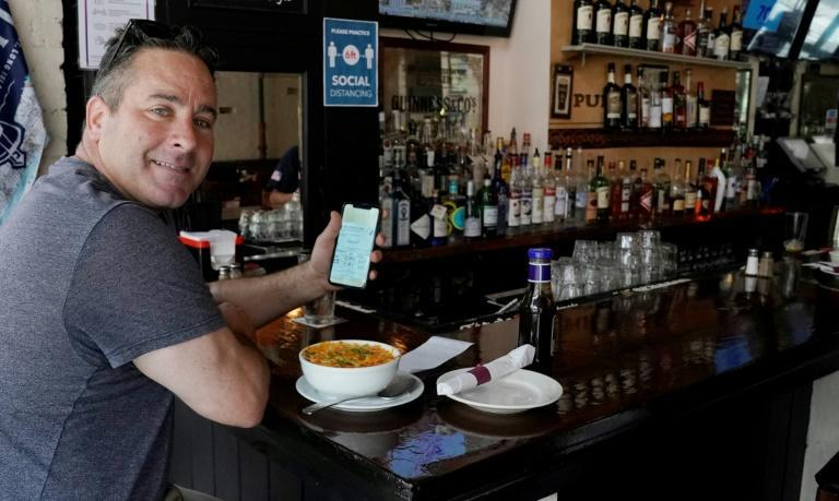 A diner holds his vaccine card as he has lunch in a restaurant in New York's Upper West Side on August 17, 2021