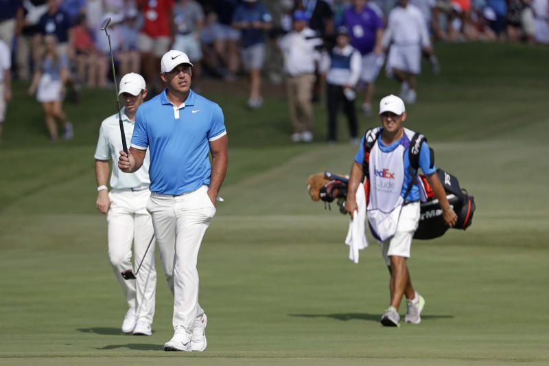 Brooks Koepka, center, and Rory McIlroy, left, of Northern Ireland,  walk down the 18th fairway during the final round of the World Golf Championships-FedEx St. Jude Invitational Sunday, July 28, 2019, in Memphis, Tenn. Koepka won the tournament. (AP Photo/Mark Humphrey)