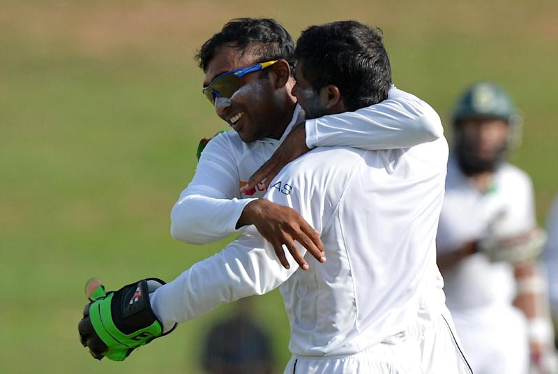 Sri Lanka's Mahela Jayawardene (L) and wicketkeeper Niroshan Dickwella celebrate the dismissal of South Africa's Faf du Plessis during the second day of the second Test in Colombo on July 25, 2014 (AFP Photo/Ishara S.Kodikara)