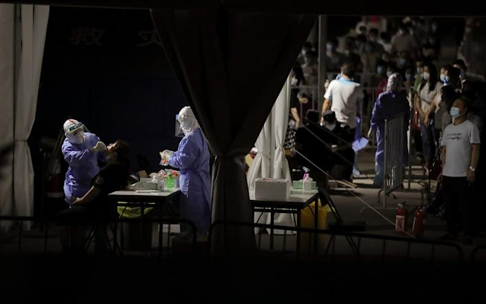 A nurse wearing a protective suit and mask takes test from a person who either visited or lives near the Xinfadi Market - Getty