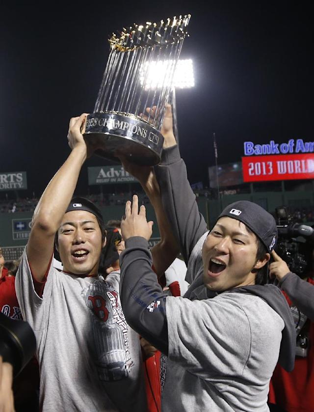 Boston Red Sox relief pitcher Koji Uehara, left, holds the championship trophy with teammate Junichi Tazawa after defeating the St. Louis Cardinals in Game 6 of baseball's World Series Wednesday, Oct. 30, 2013, in Boston. The Red Sox won 6-1 to win the series. (AP Photo/Elise Amendola)