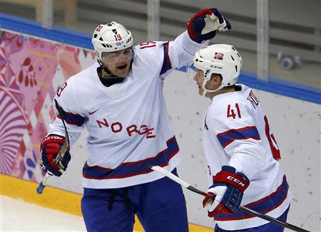 Norway's Per-Age Skroder (L) celebrates his goal against Austria with teammate Patrick Thoresen during the second period of their men's preliminary round ice hockey game at the Sochi 2014 Winter Olympic Games, February 16, 2014. REUTERS/Grigory Dukor