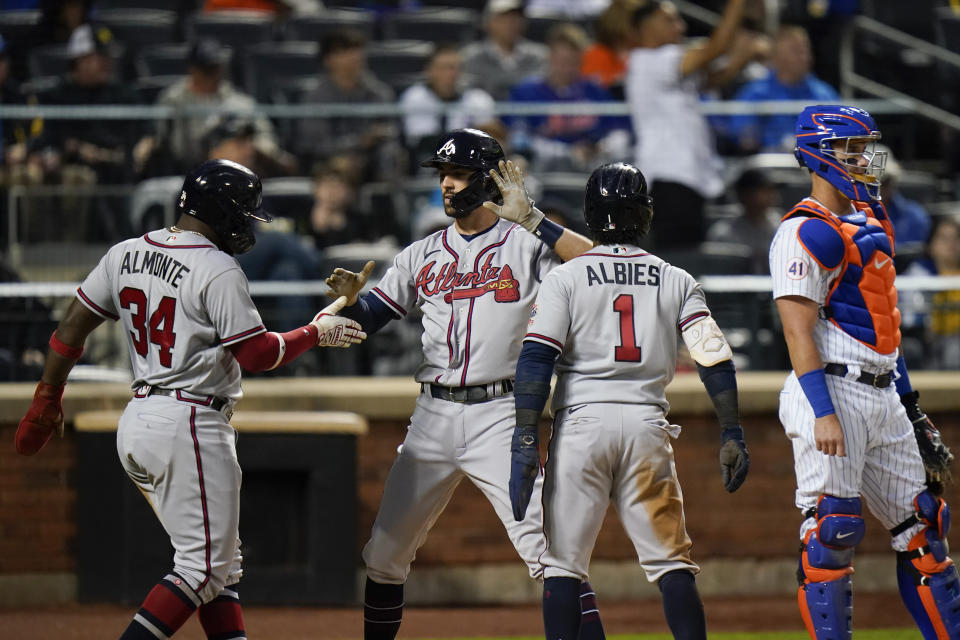 Atlanta Braves' Dansby Swanson celebrates with teammates Abraham Almonte (34) and Ozzie Albies (1) after hitting a three-run home run as New York Mets catcher James McCann looks away during the third inning of a baseball game Tuesday, June 22, 2021, in New York. (AP Photo/Frank Franklin II)