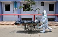 Healthcare workers transfer the body of a person who died from the coronavirus disease (COVID-19), inside a hospital premises in Kolkata