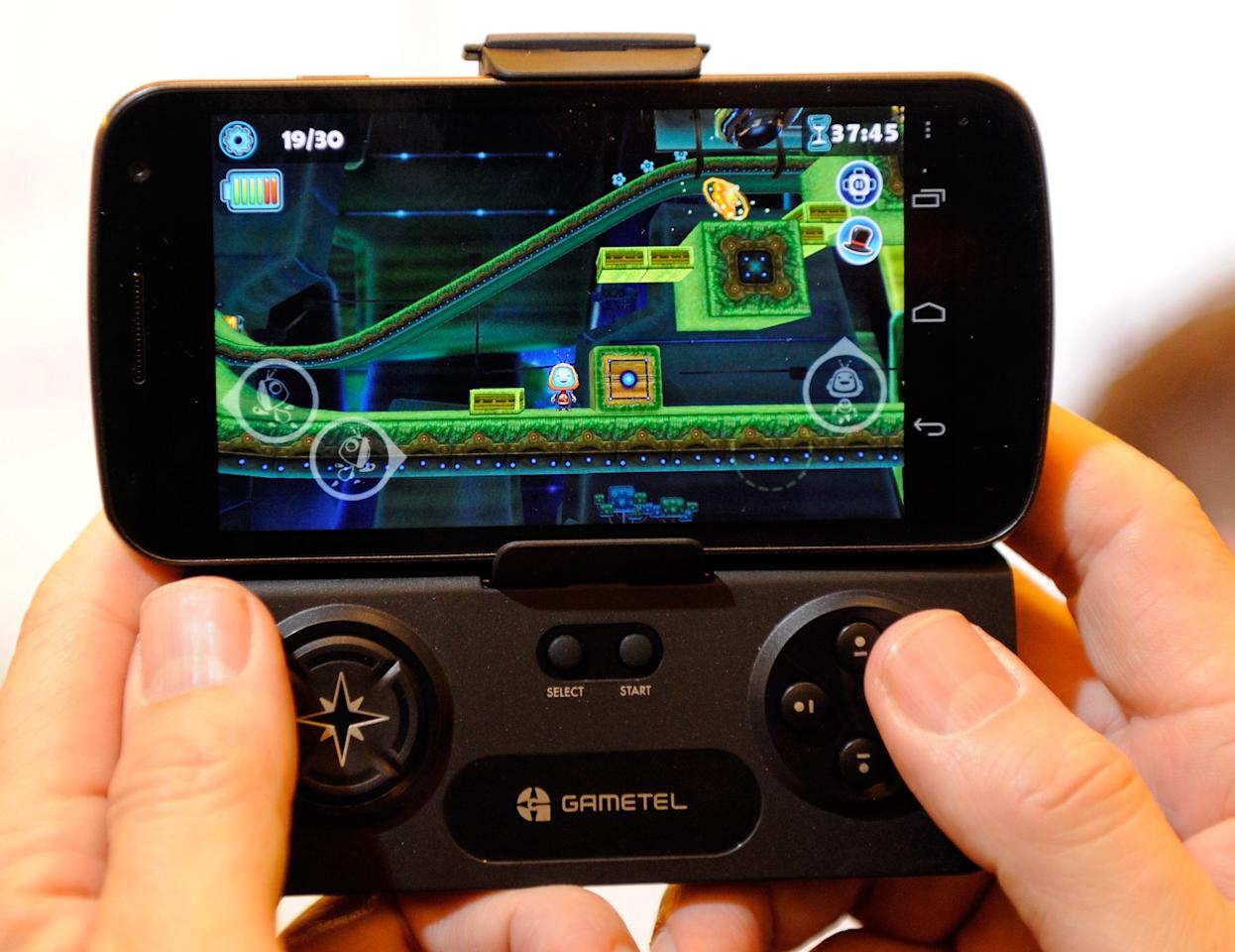 LAS VEGAS, NV - JANUARY 08:  A Gametel wireless controller by Fructel is used to play a video game on a smartphone during a press event at The Venetian for the 2012 International Consumer Electronics Show (CES) January 8, 2012 in Las Vegas, Nevada. The device can turn most Android or iOS smartphones or tablets into portable gaming consoles. CES, the world's largest annual consumer technology trade show, runs from January 10-13 and is expected to feature 2,700 exhibitors showing off their latest products and services to about 140,000 attendees.  (Photo by Ethan Miller/Getty Images)