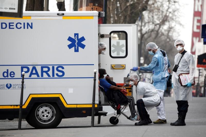 FILE PHOTO: French SAMU rescue team and firefighters wearing protective suits evacuate a patient in a street in Paris