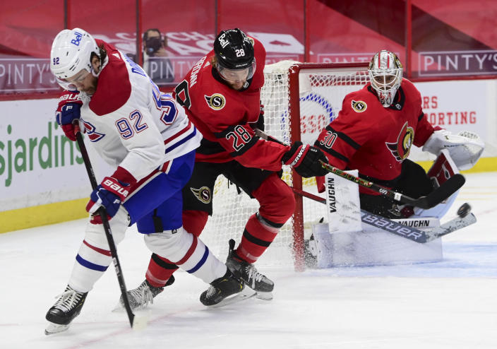 Ottawa Senators right wing Connor Brown (28) clears the puck away from Montreal Canadiens left wing Jonathan Drouin (92) as Senators goaltender Matt Murray (30) looks on during the first period of an NHL hockey game in Ottawa on Saturday, Feb. 6, 2021. (Sean Kilpatrick/The Canadian Press via AP)