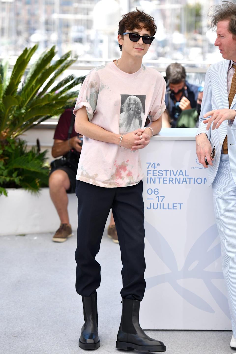 <p>Wearing a pink tee with black pants, tall boots, and Cartier jewels.</p>