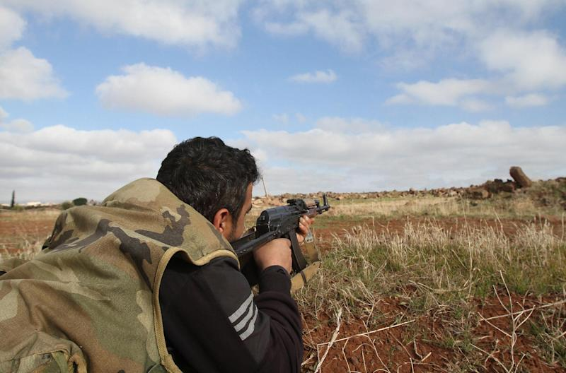 A Syrian army fighter points his rifle towards the rebel-held province of Daraa as he takes position on the green Line in Mjeimer in the mainly-Druze southern province of Suwaida on January 23, 2013