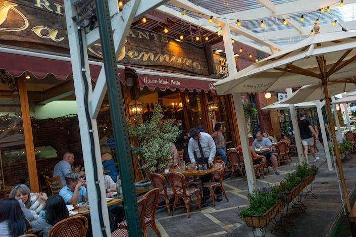 A view from the street of diners seated at sidewalk tables outside a restaurant.