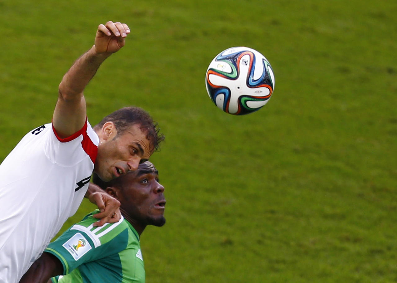 Iran's Jalal Hosseini (L) and Nigeria's Emmanuel Emenike jump for the ball during their 2014 World Cup F soccer match at the Baixada arena in Curitiba June 16, 2014. REUTERS/Amr Abdallah Dalsh (BRAZIL - Tags: SOCCER SPORT WORLD CUP)