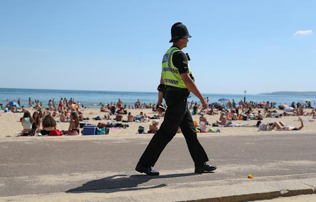 A police officer patrols along the beach in Bournemouth, Dorset, as the public are being reminded to practice social distancing. (PA/Getty)