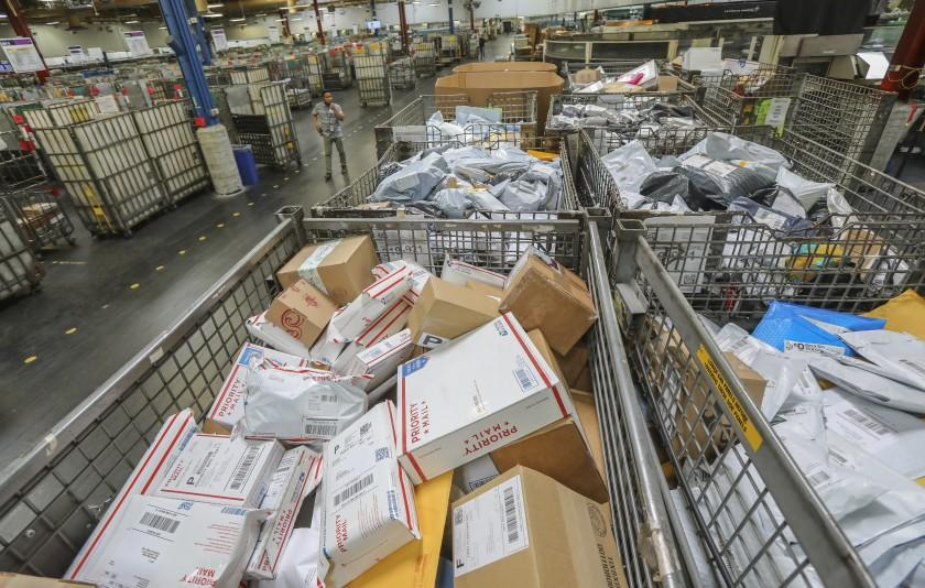 Postal workers sort parcels at Margaret L. Sellers Processing and Distribution Center at the USPS Carmel Mountain Post Office on May 14, 2020 in San Diego, California. The post office is seeing a huge increase in the amount of packages its handling.