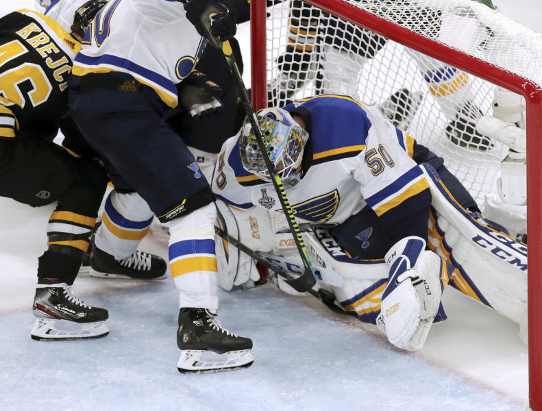 St. Louis Blues goaltender Jordan Binnington, right, stops a shot at the goal line as Boston Bruins' David Krejci, left, of the Czech Republic, pokes at it during the third period in Game 5 of the NHL hockey Stanley Cup Final, Thursday, June 6, 2019, in Boston. A video review confirmed there was no goal on the play. (AP Photo/Charles Krupa)