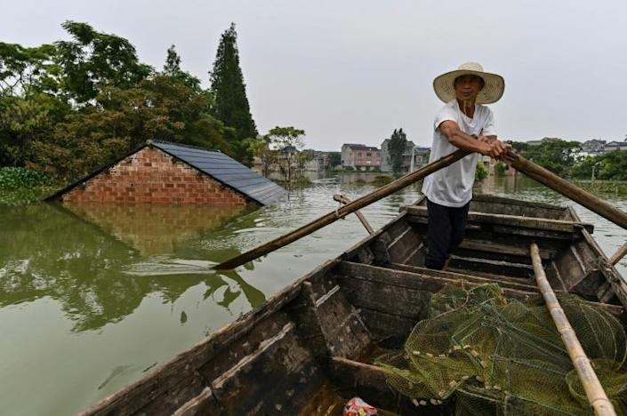 A fisherman rows his boat past the roof a house seen above the water level of a flooded area due to torrential rains in Longkou village of Poyang county in China's central Jiangxi province. (AFP Photo/Hector RETAMAL)