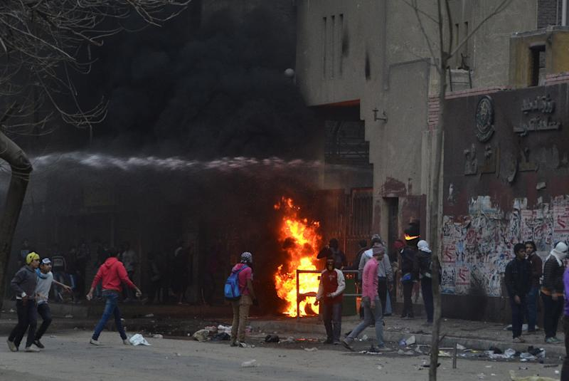 Supporters of Egypt's ousted President Mohammed Morsi damage a police building as water canon from the building is used to extinguish flames in Cairo's Ain Shams district, Egypt, Friday, Feb. 7, 2014. Clashes between Egyptian security forces and Islamist protesters left one person dead in a province southwest of Cairo on Friday while two home-made bombs targeting policemen wounded six people in a bridge in the capital, officials said. (AP Photo/Mostafa Darwish)