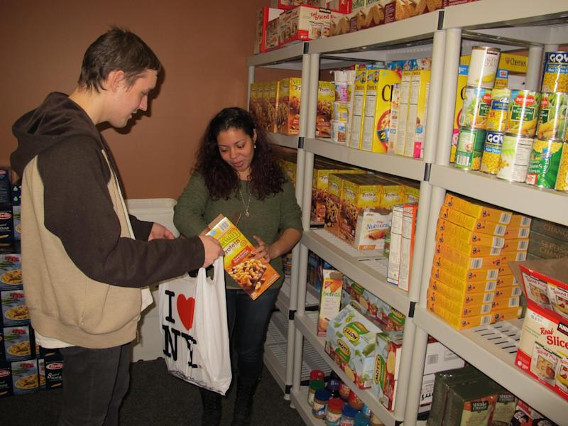 In this photo taken on Tuesday, March 4, 2014, at Stony Brook University, students Ruby Escalera-Nater and Will Addison fill a bag of food to give to guests at the college's recently opened food pantry. Officials say there are a growing number of food pantries opening on college campuses across the country to assist students contending with rising education costs.(AP Photo/Frank Eltman)